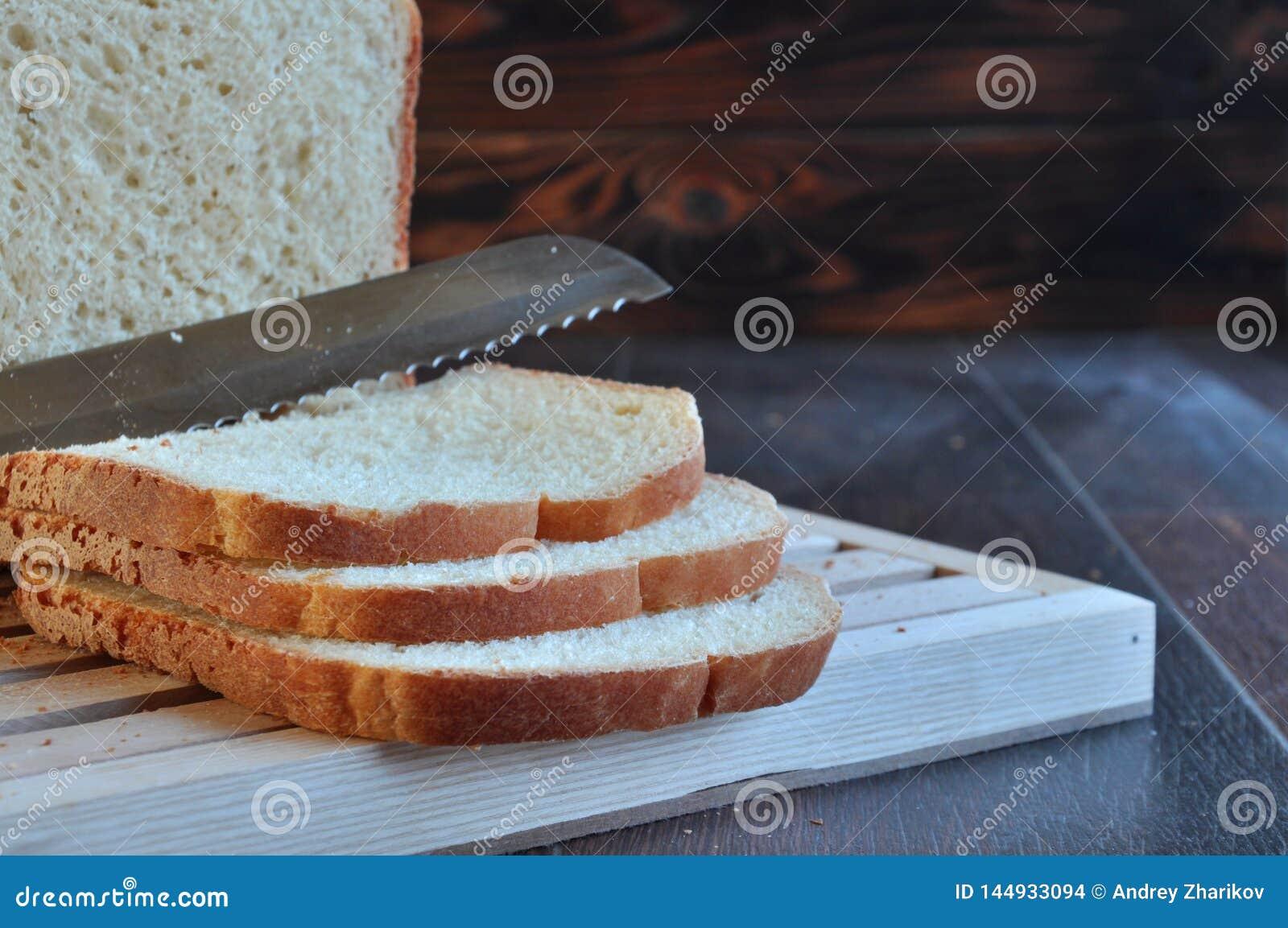 Pain avec du beurre et le couteau sur le conseil en bois