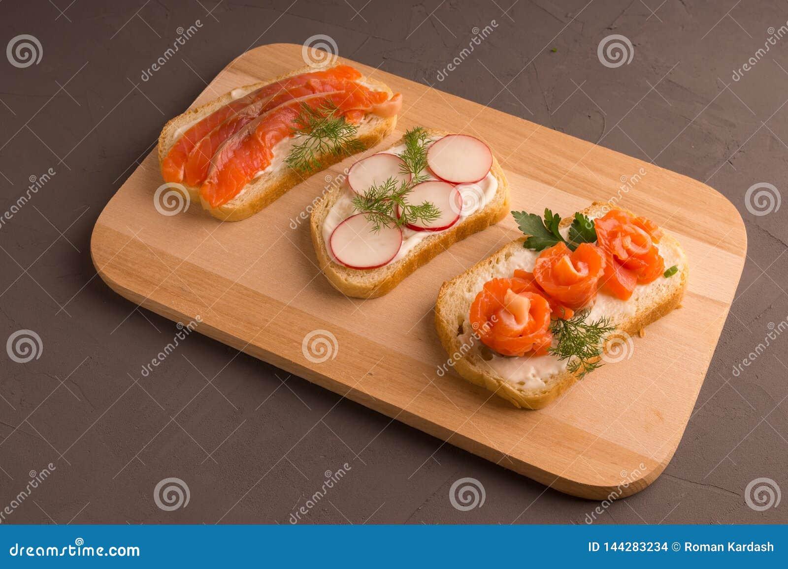 Pain coupé en tranches avec les tranches saumonées, tomates-cerises