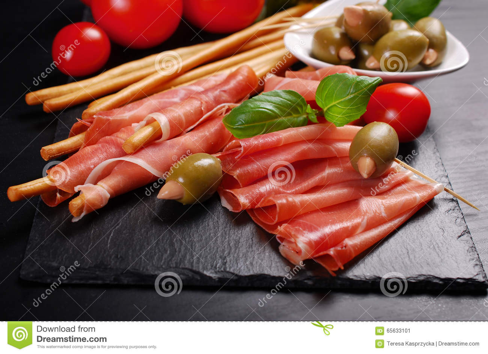 Pain de bâton de Grissini avec du jambon sur le conseil noir