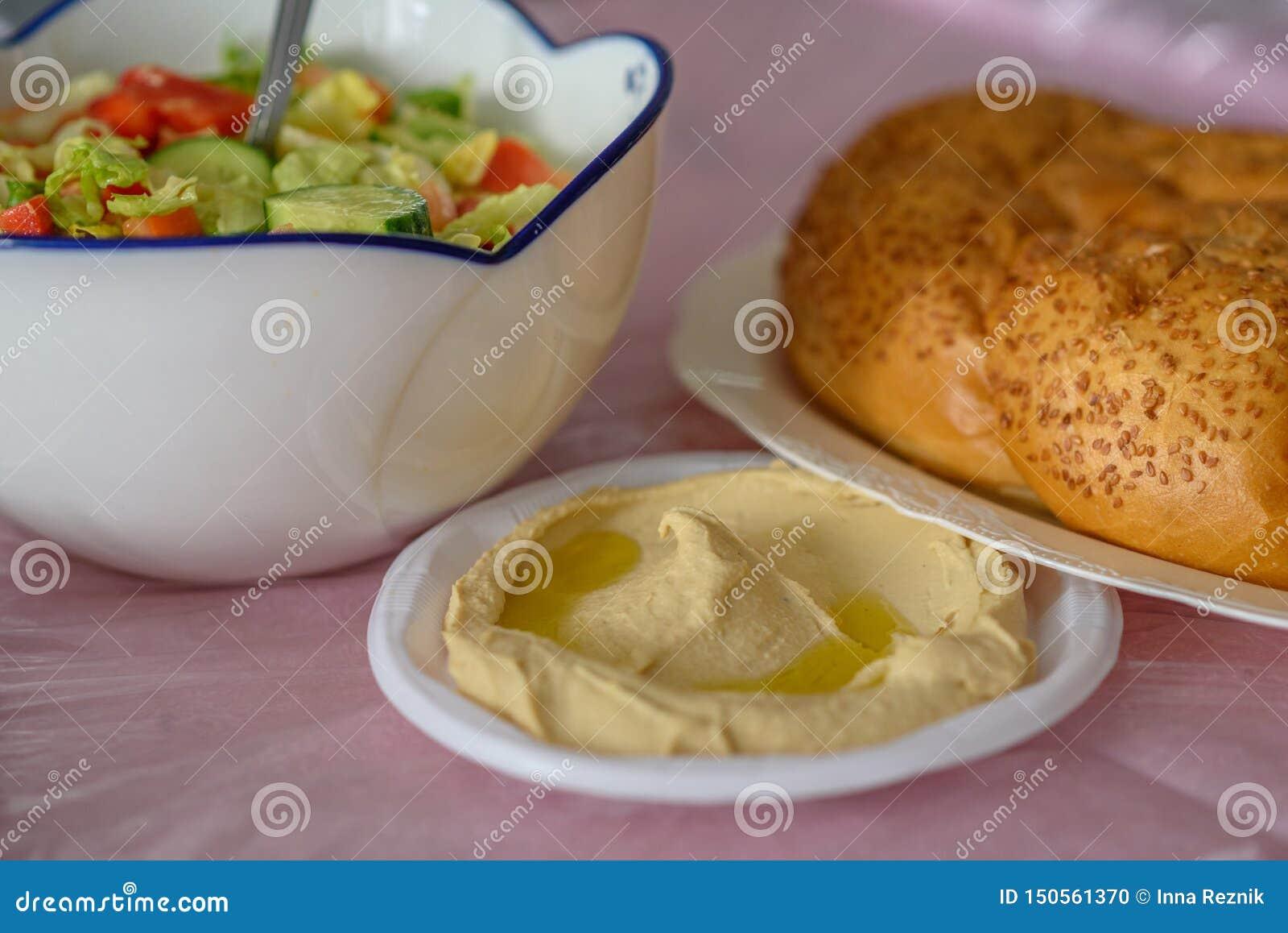 Pain de pain du sabbat sur une table pour le repas de Shabbat et houmous fait maison traditionnel, salade sur la table rose Cuisi