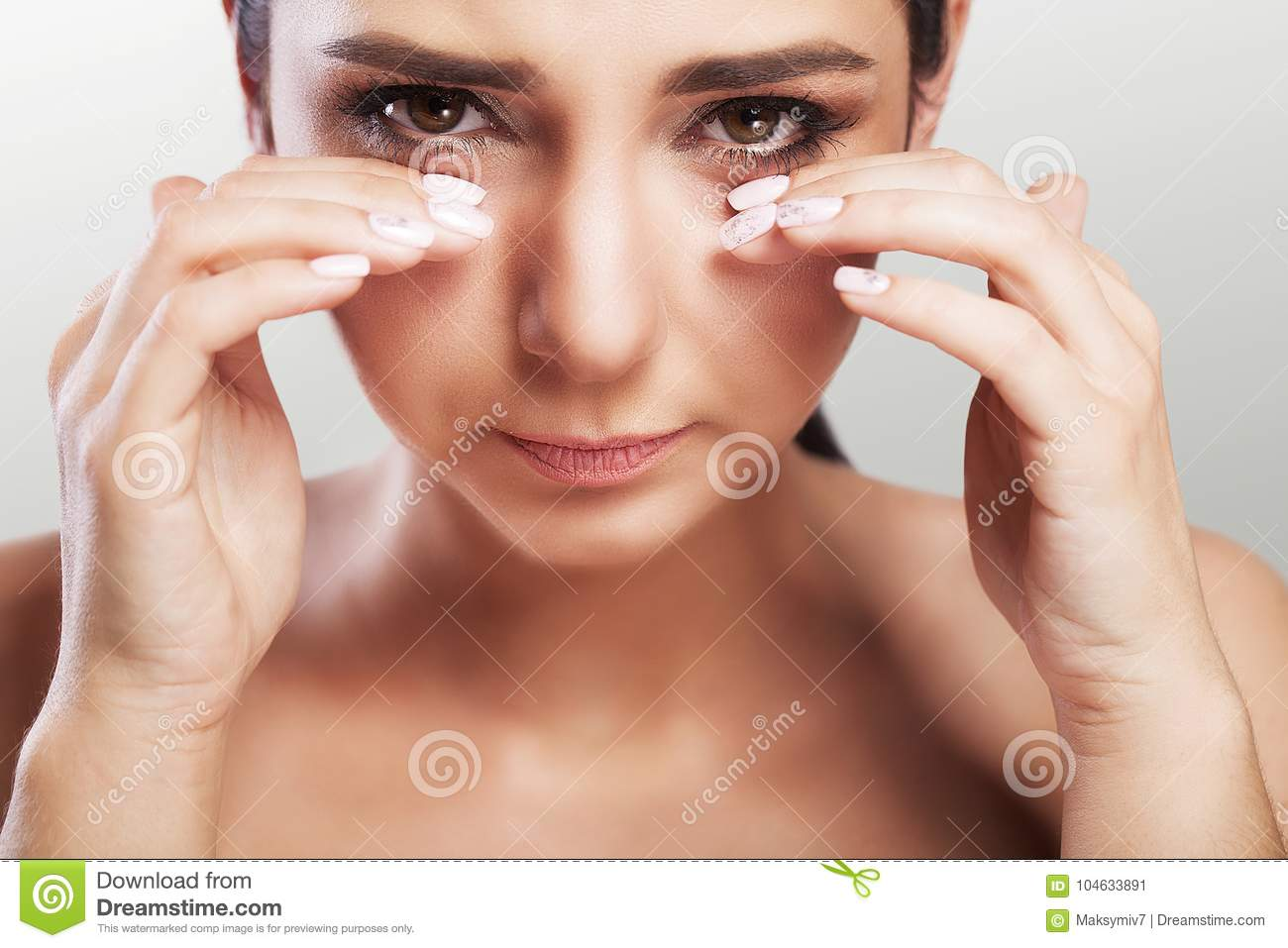 Pain in the eye area. A beautiful unhappy woman who suffers from severe pain in the eye area. Portrait of a sad woman`s feeling o