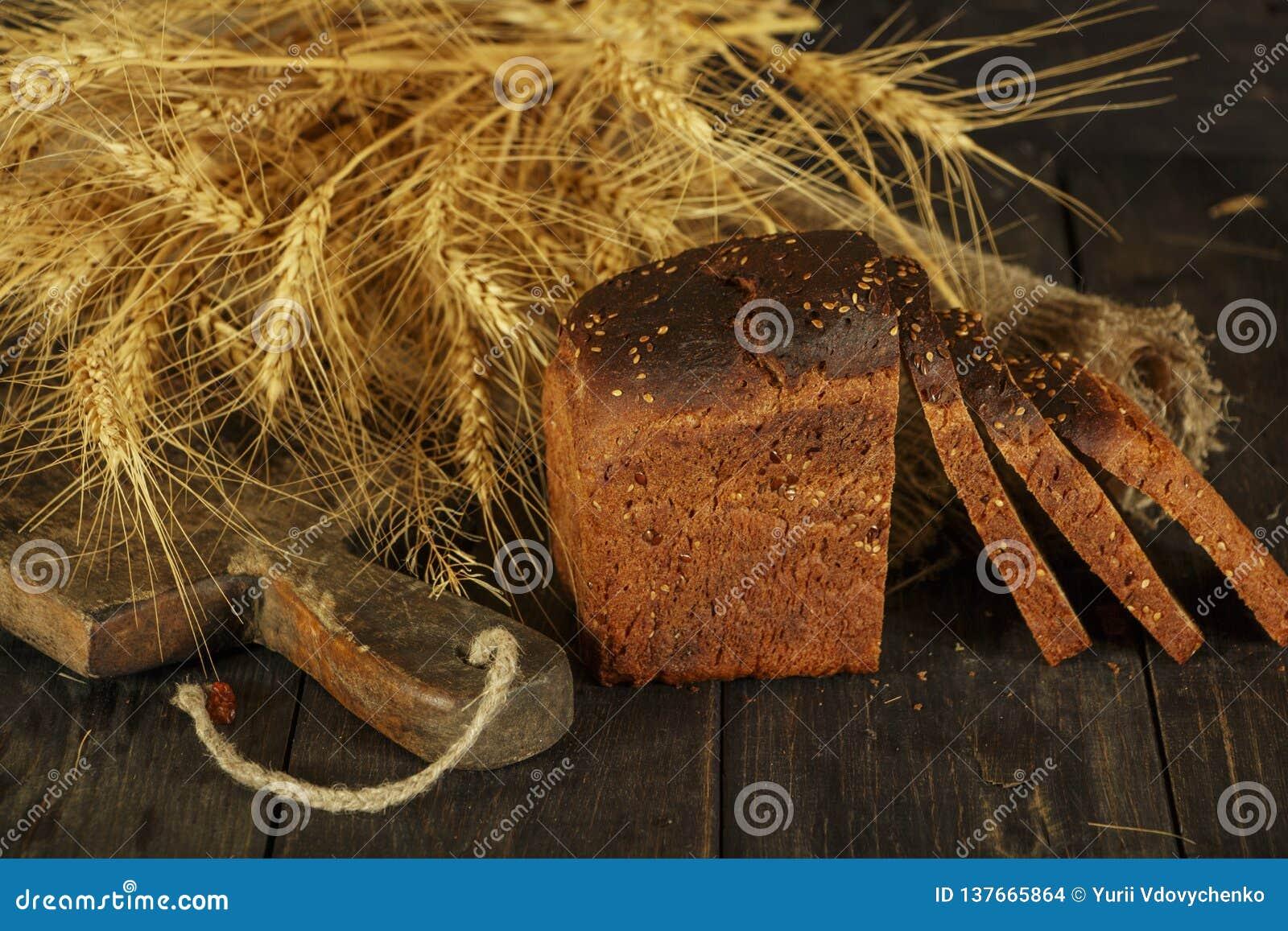Pain fait maison frais avec la transitoire de blé entier sur un fond en bois noir Pain frais avec une oreille de blé
