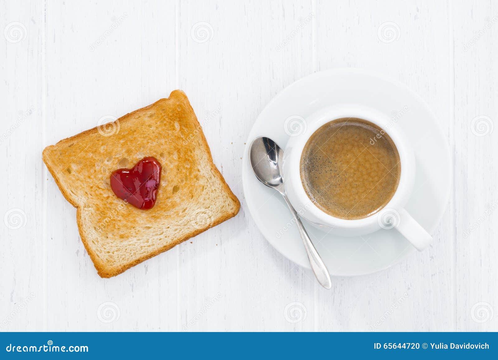 Pain grillé dans la forme de coeur avec de la confiture de fruit et la tasse de café