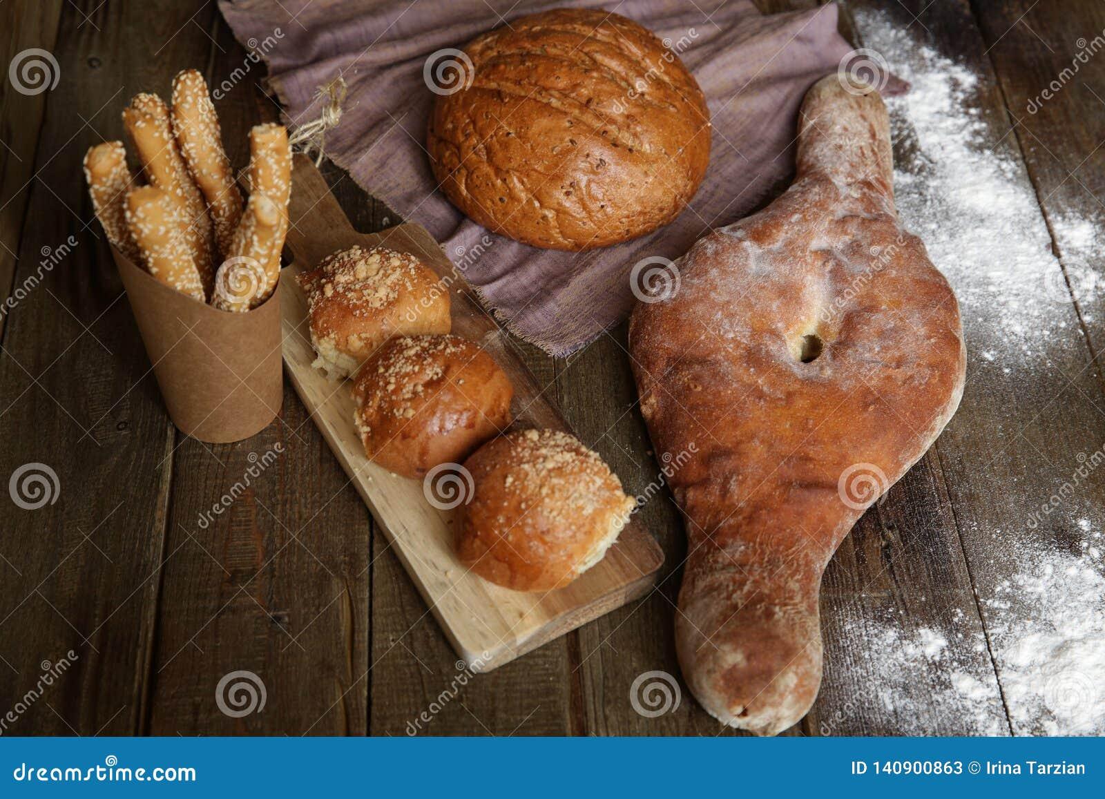 Pain sur une table rustique en bois, petits pains de pain sur un conseil en bois et des batons de pain avec les graines de sésame