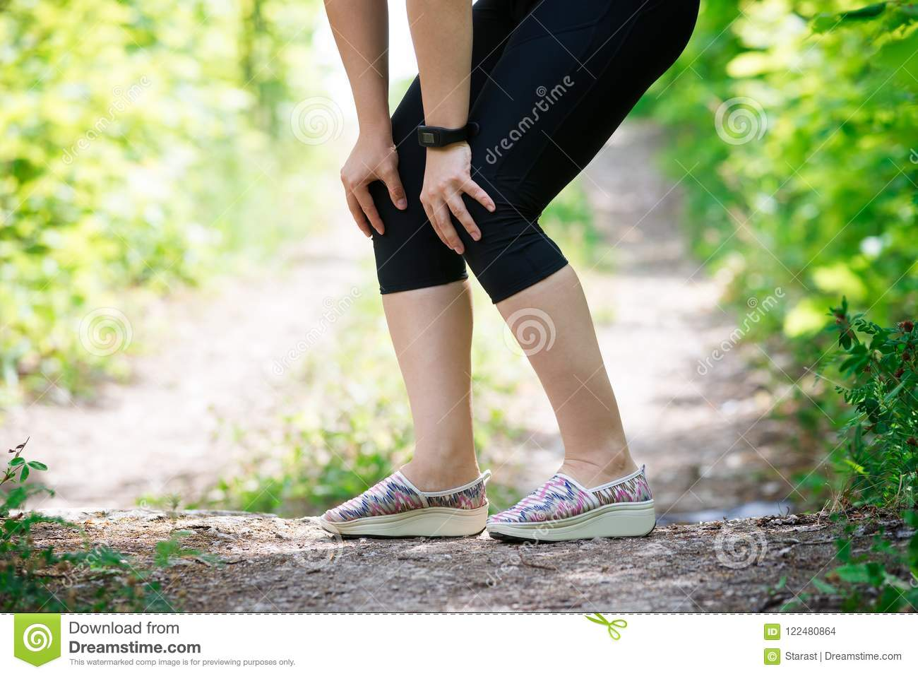 Pain in woman`s knee, massage of female leg, injury while running, trauma during workout