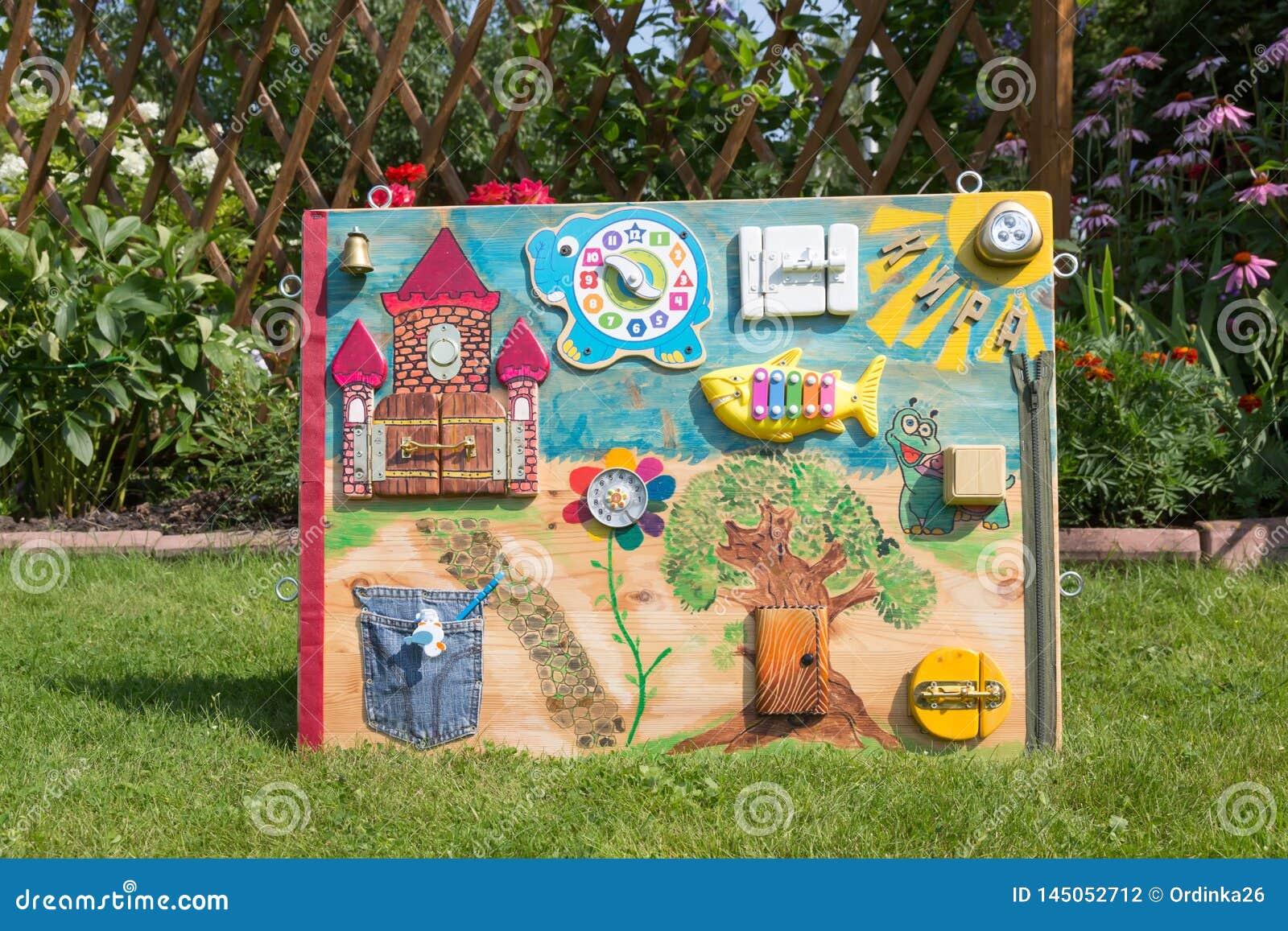 Painel caseiro do brinquedo do bebê do montessori no gramado verde do fundo