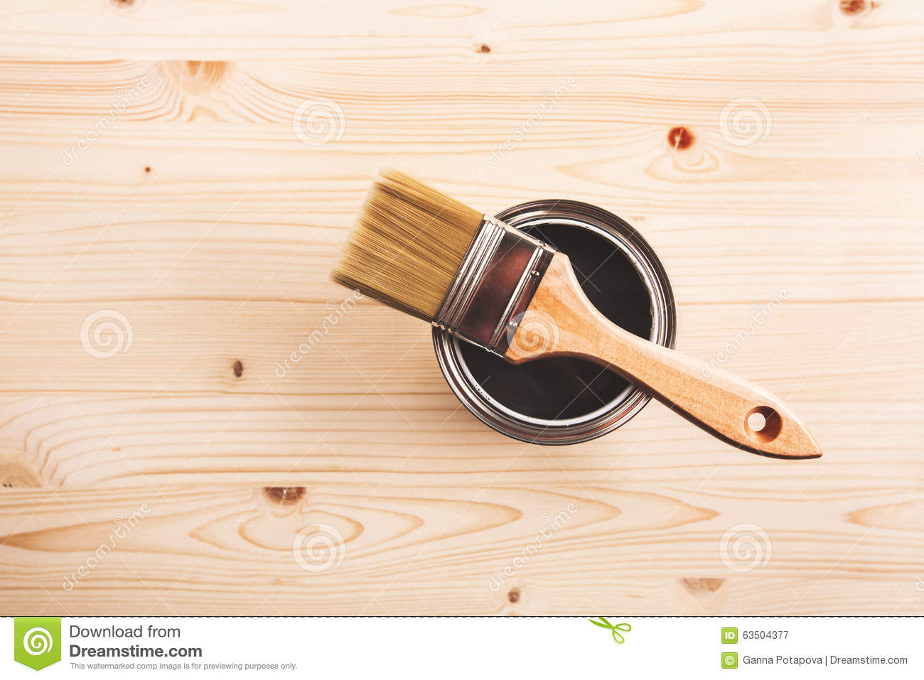 paint brush on can lying on wooden clean table. Top view. Copyspace