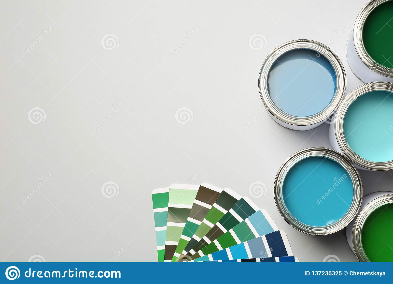 Paint cans and color palette on white background, top view.