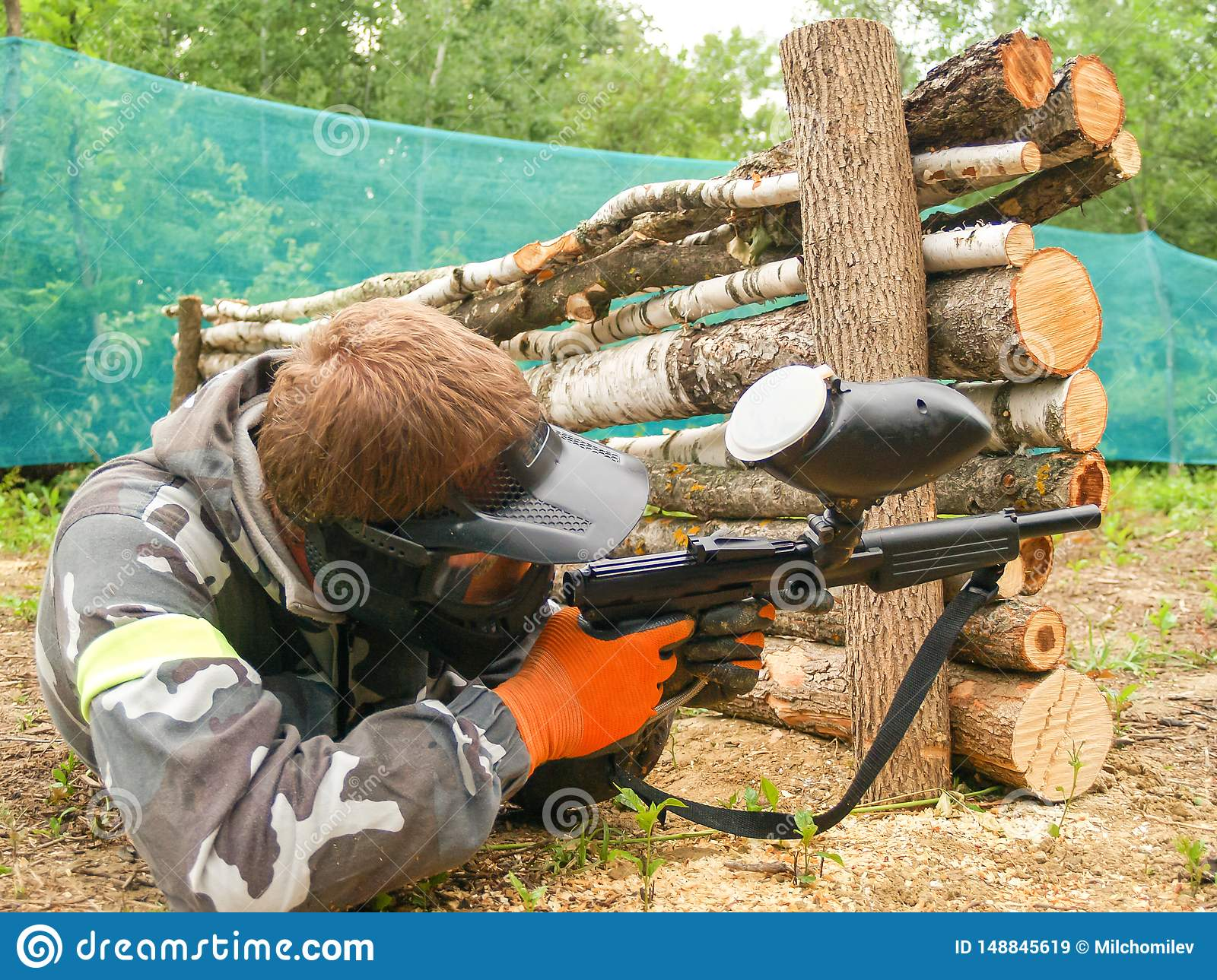 A paintball player who is ready to shoot from hiding. Lying on the ground and shooting