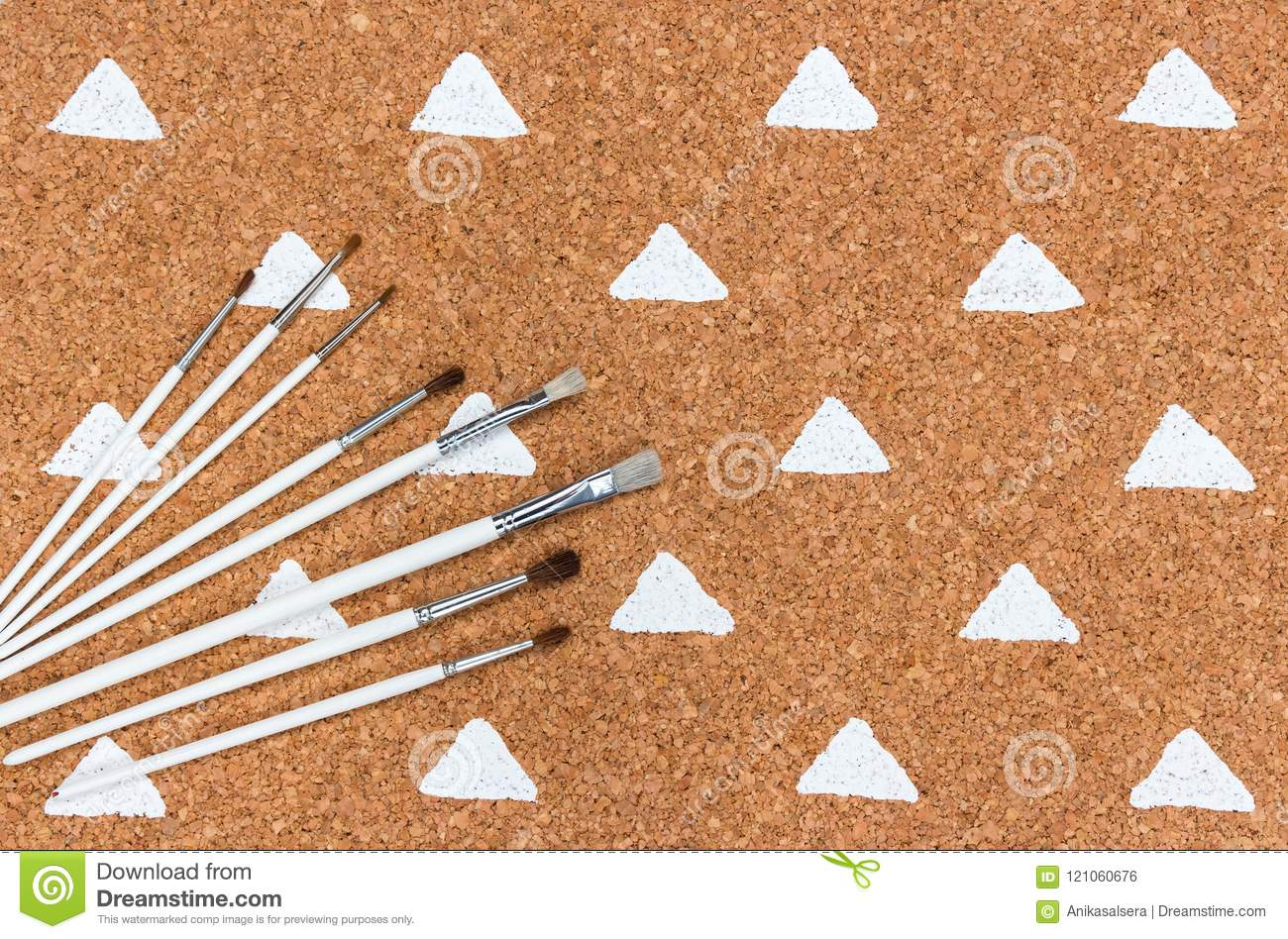 Paintbrushes on cork background with painted triangles