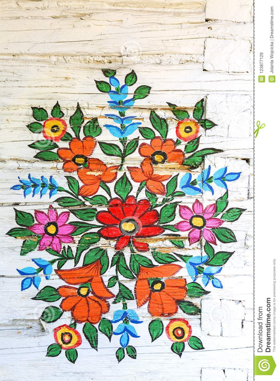 Painted beautiful floral pattern on the facade of an old house, Zalipie, Poland.