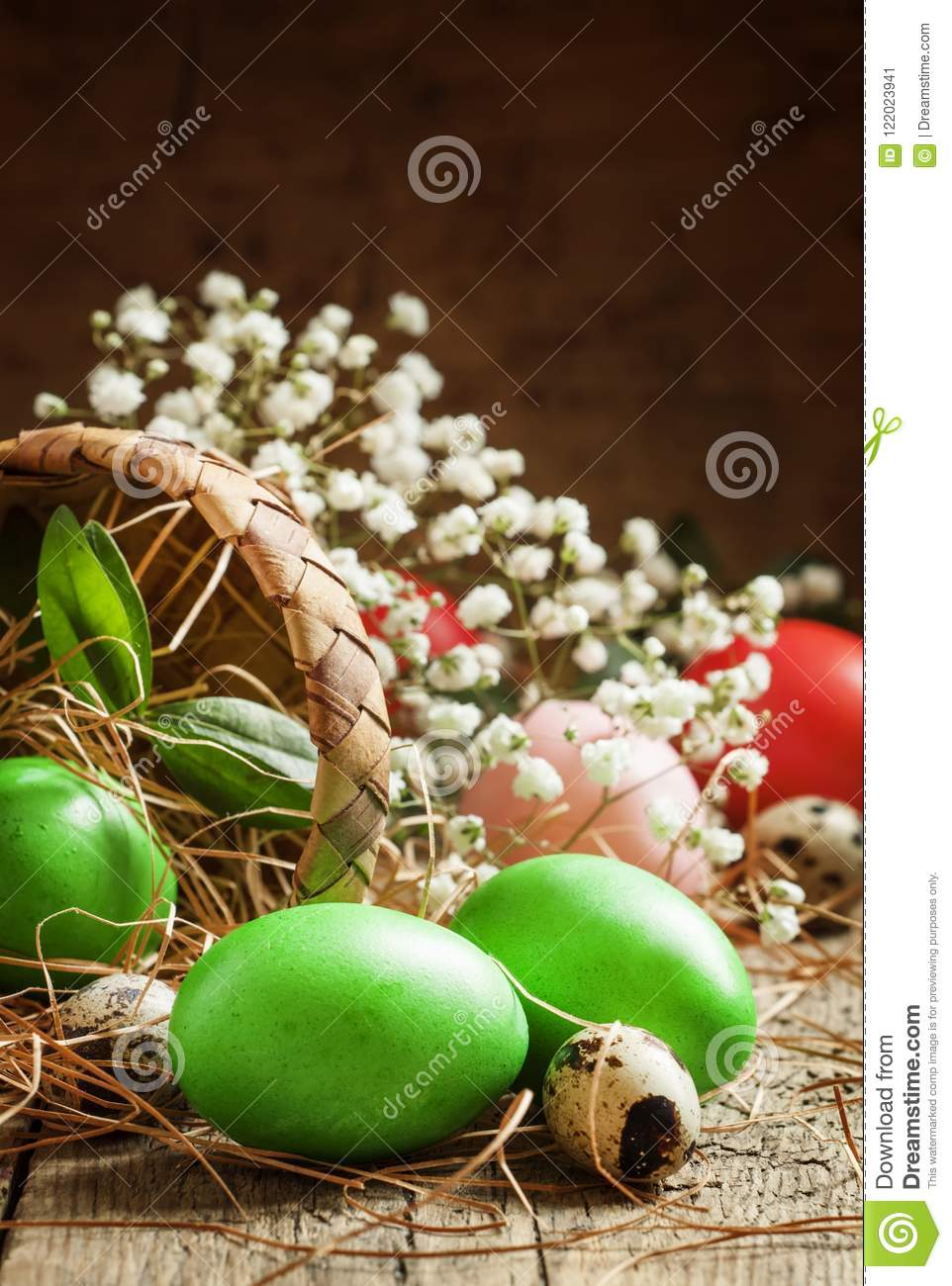 Painted green Easter eggs poured woven birch bark baskets in straw on the old wooden table in rustic style, selective focus