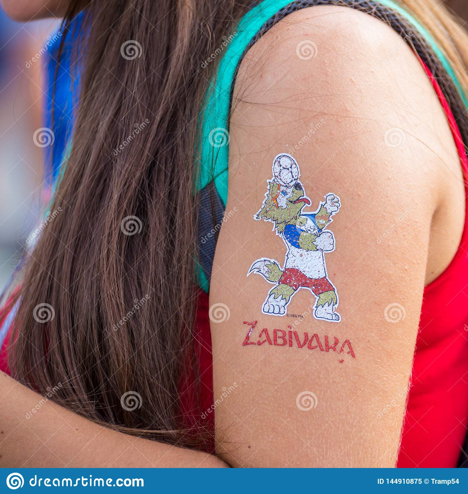 Painted mascot of the World Cup soccer Wolf zabiyaka on the hand of the girl