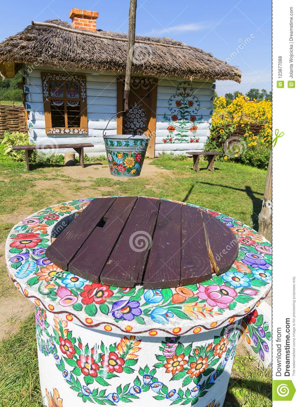 Painted old wooden cottage, well and pail, decorated with a hand painted flowers, Zalipie, Poland