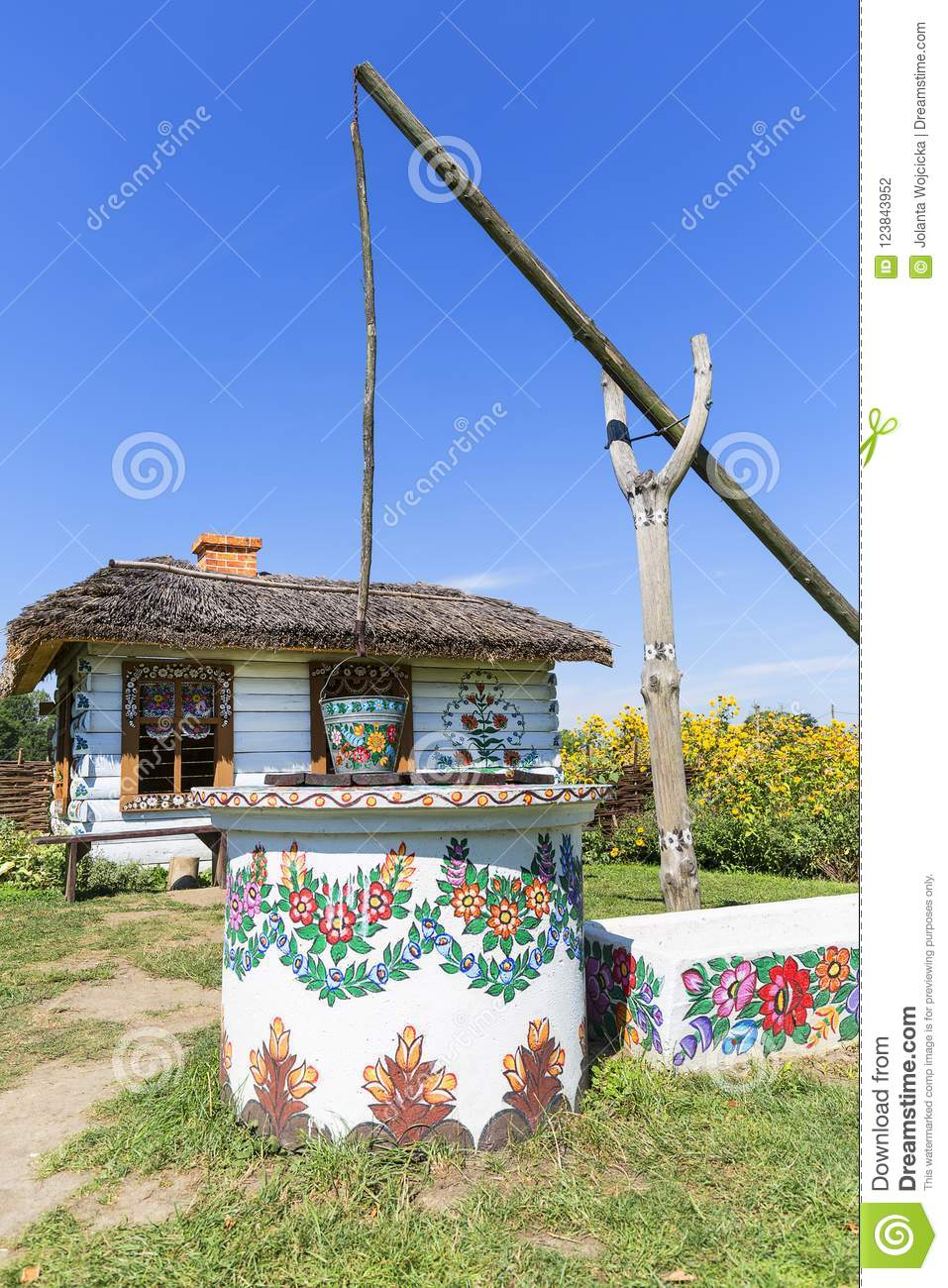 Painted old wooden cottage, well and pail,folk art, Zalipie, Poland