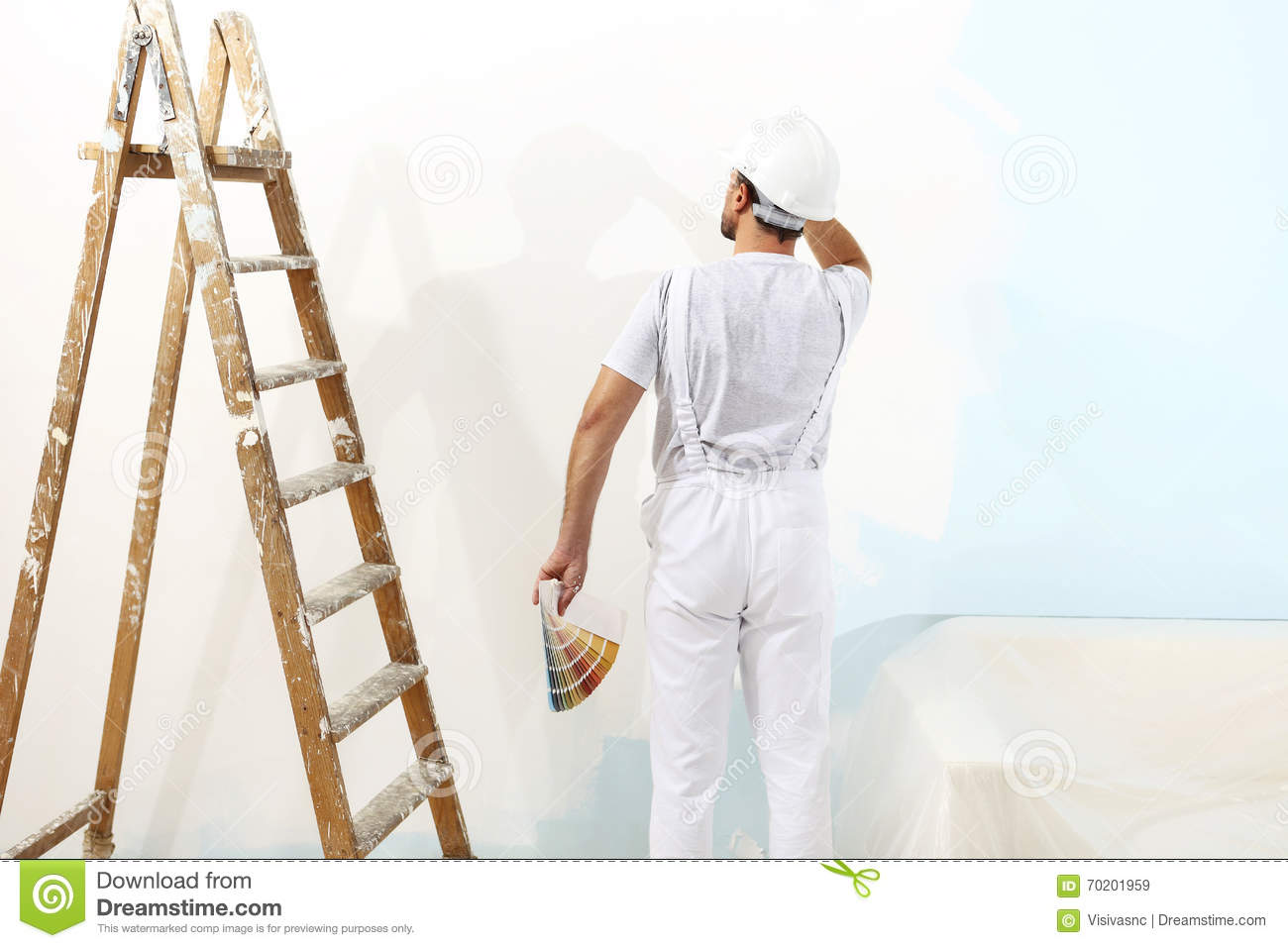 Painter man at work with color swatches samples, wall painting