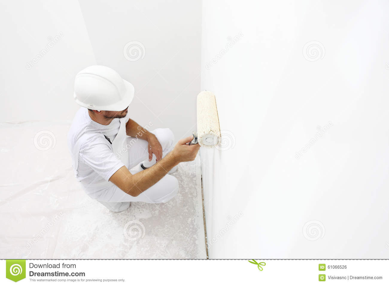 Painter man at work with a paint roller, wall painting