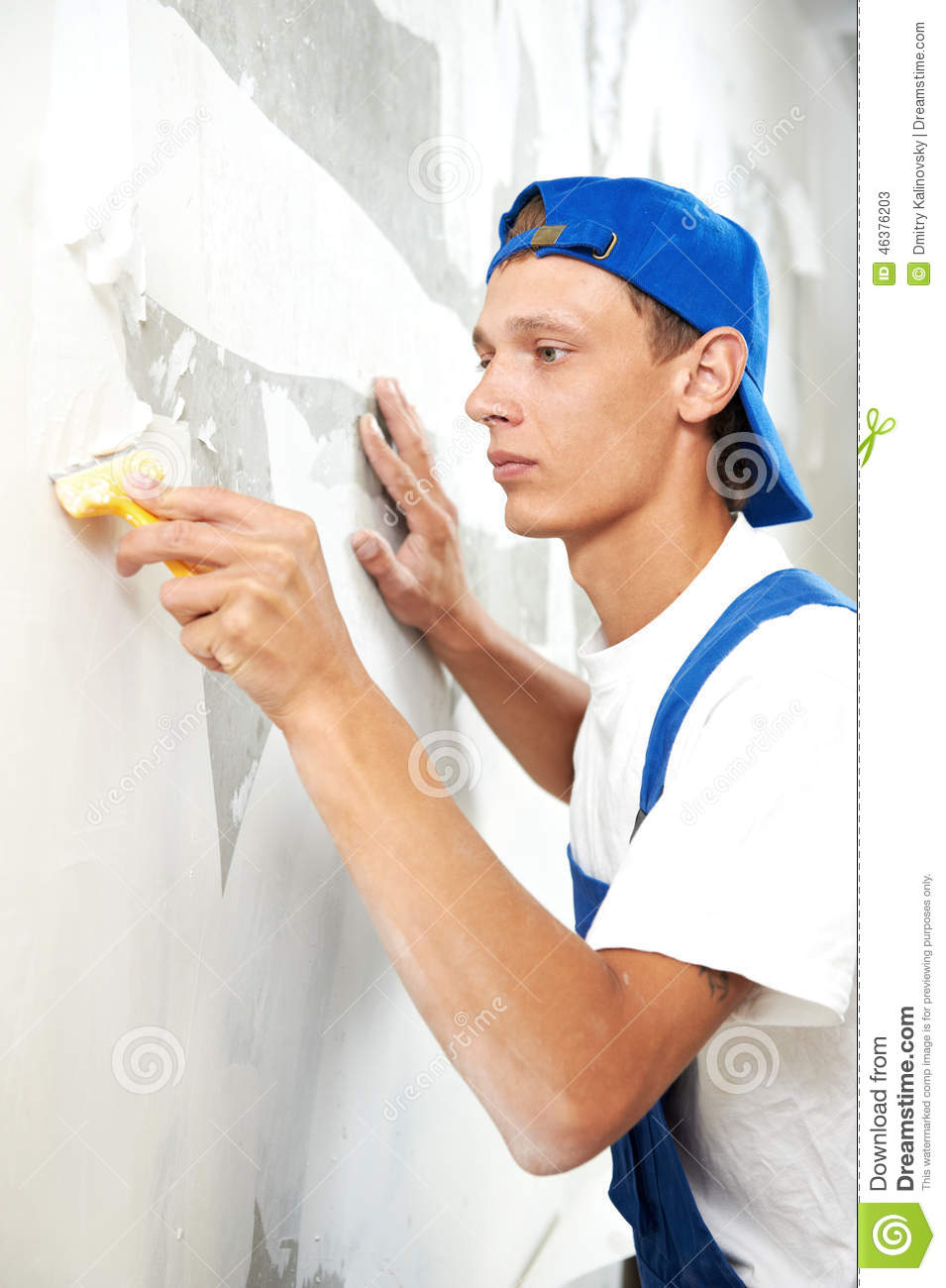 Painter worker peeling off wallpaper stock image image for Wallpaper home renovation