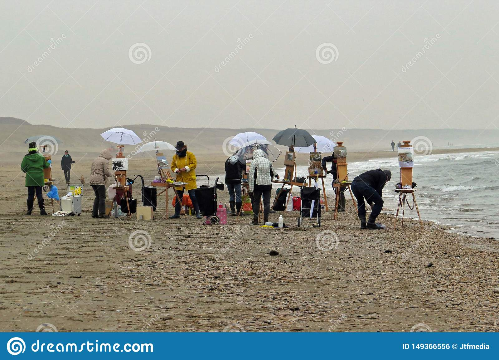 Painters / artists with their easels painting at the foggy beach in Katwijk, Netherlands