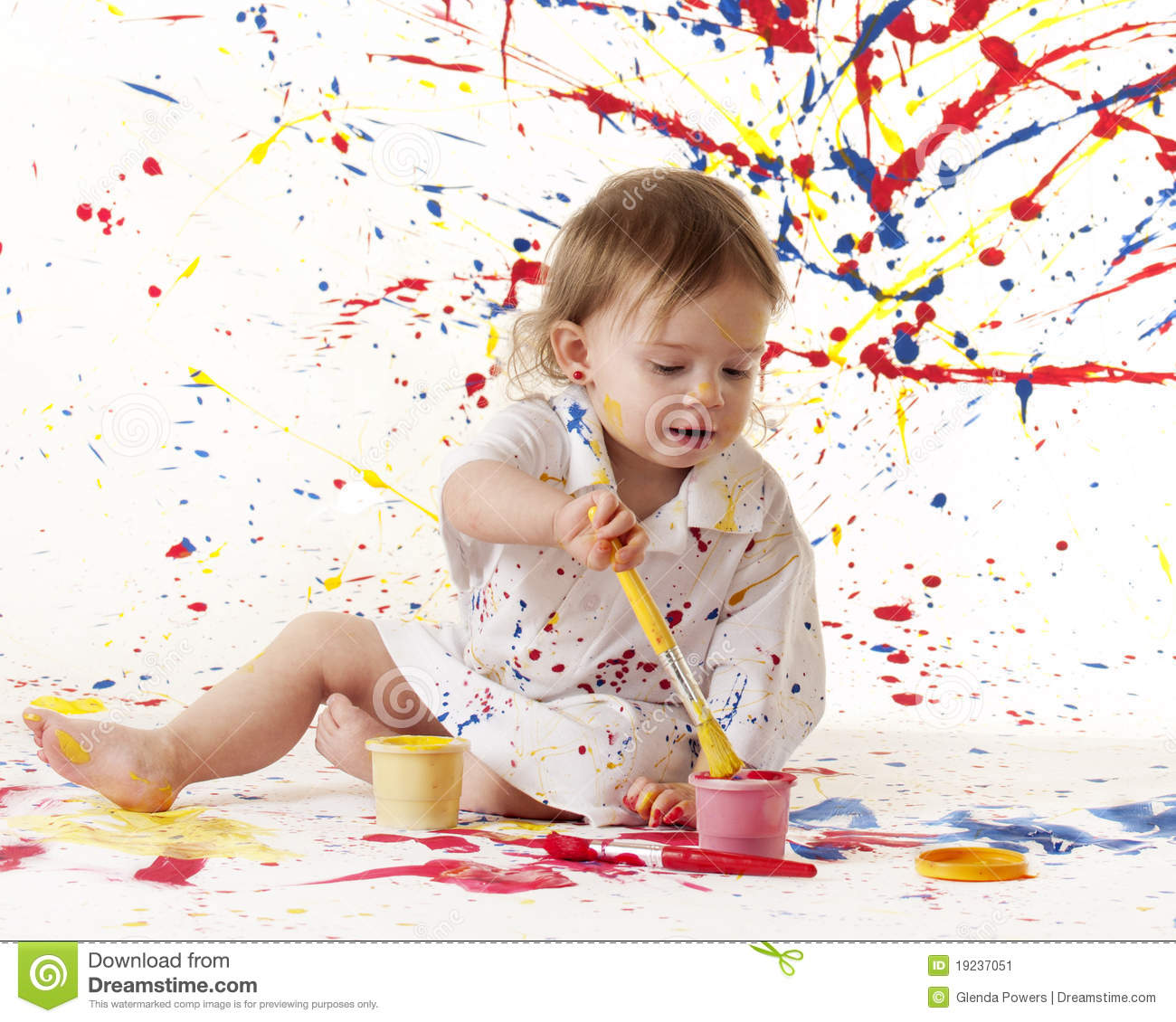 An adorable baby girl painting against a splattered paint background