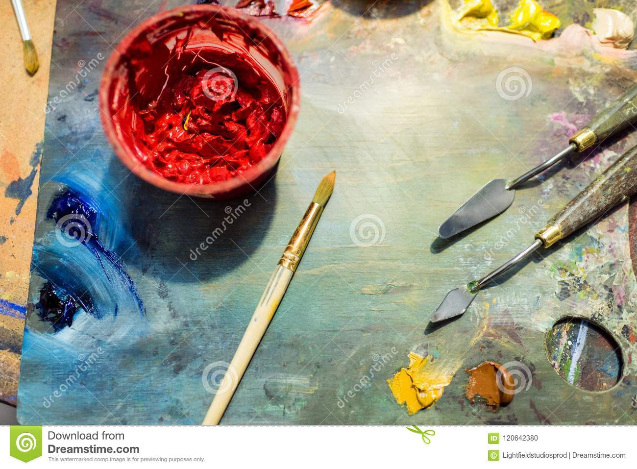 painting brushes, palette and red poster paint on wooden table