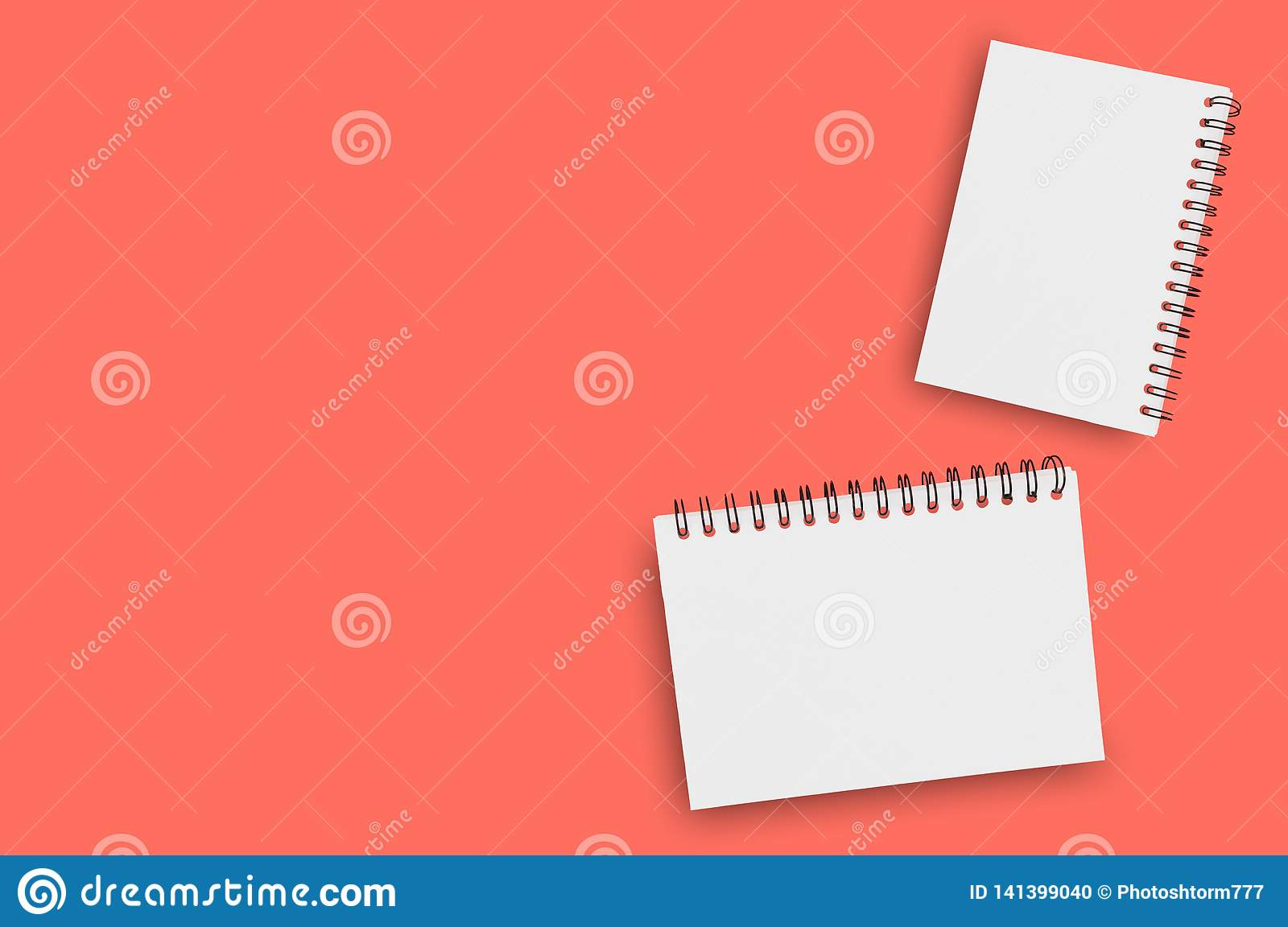 Pair of blank paper notepads with spiral wire for note or drawing on background of living coral color. Copy space for your text