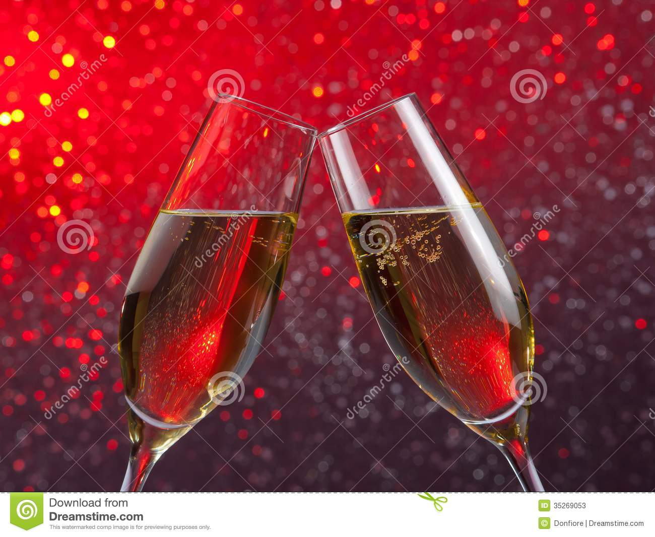 pair of a champagne flutes with gold bubbles on red and violet light