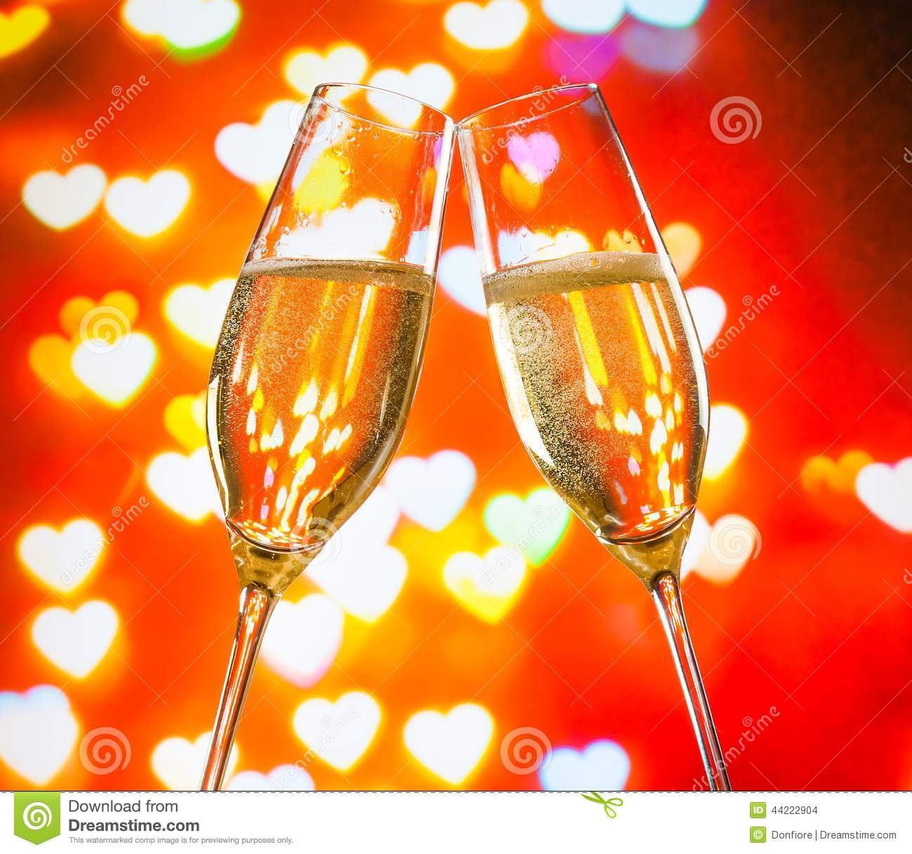 A Pair Of Champagne Flutes With Golden Bubbles On Hearts
