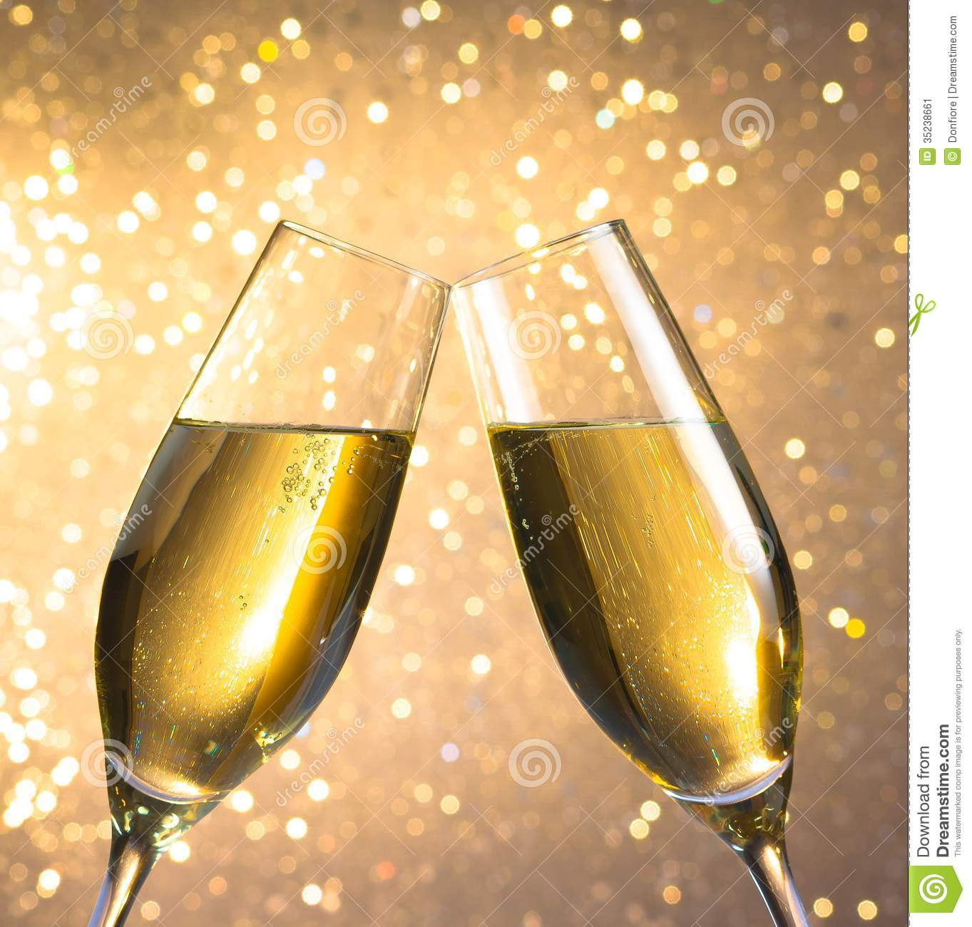 pair of a champagne flutes with golden bubbles on light. Black Bedroom Furniture Sets. Home Design Ideas