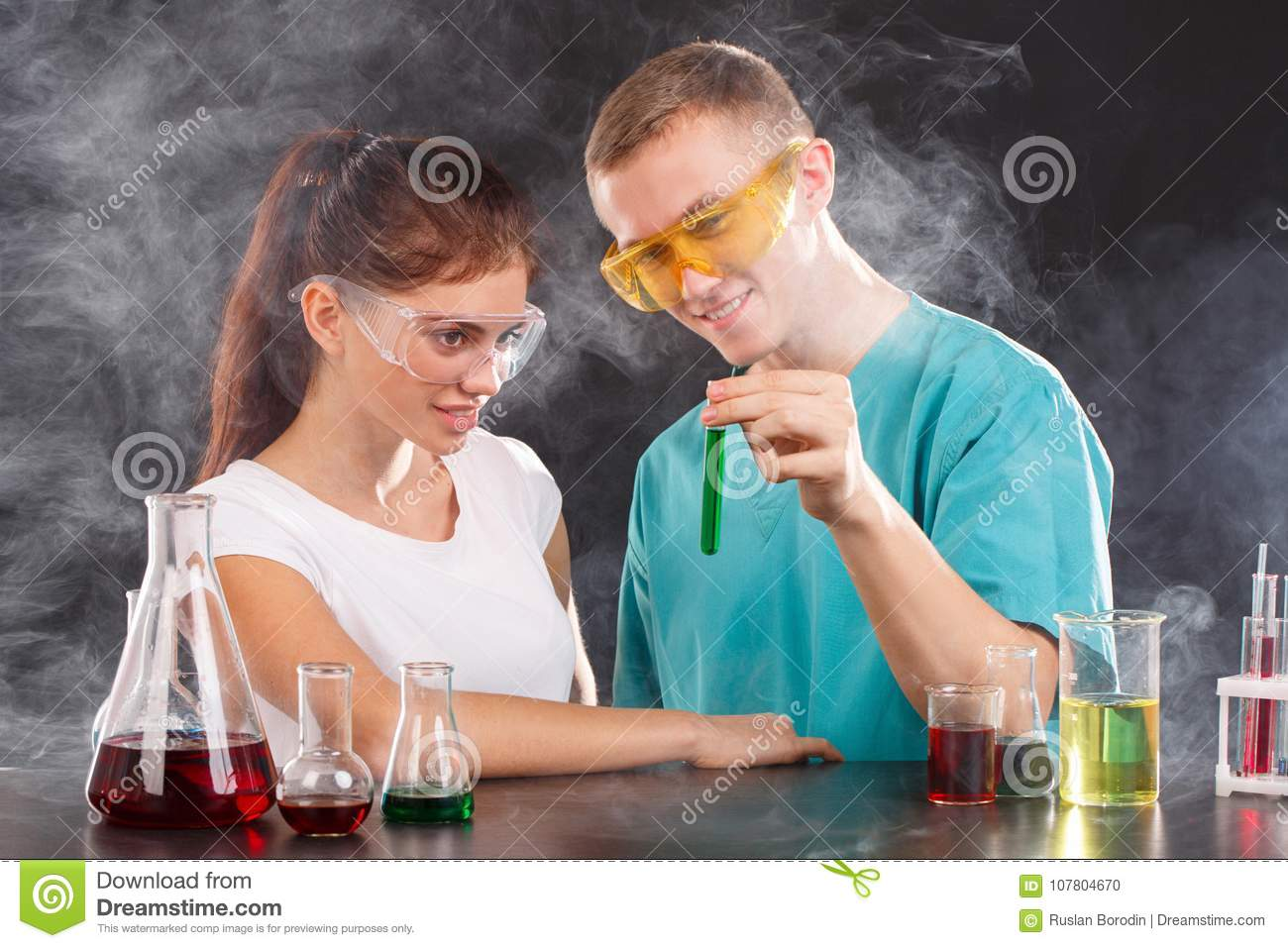 A pair of chemists examine a flask with a green liquid. The concept of science.