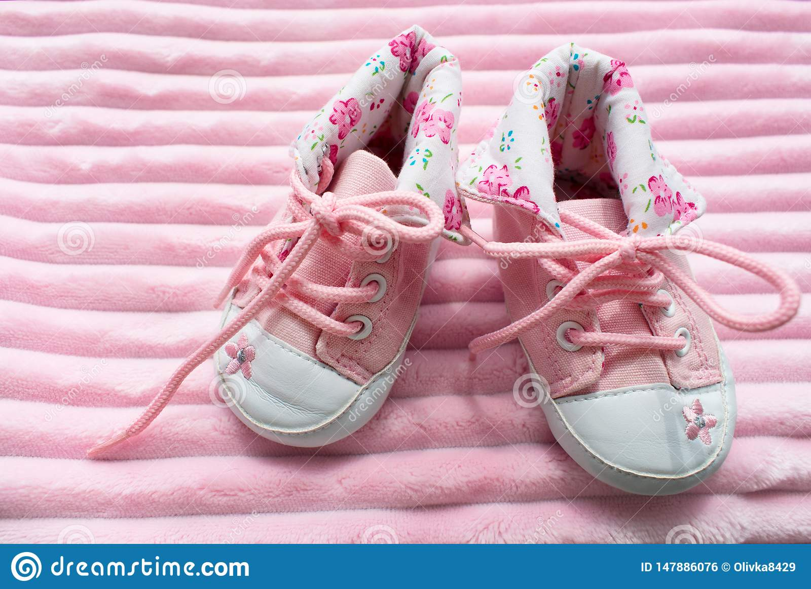 A pair of children`s sneakers for girls on a pink background