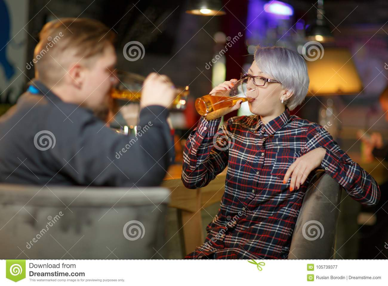 A pair are drinking beer in a bar. Indoors in a public place.