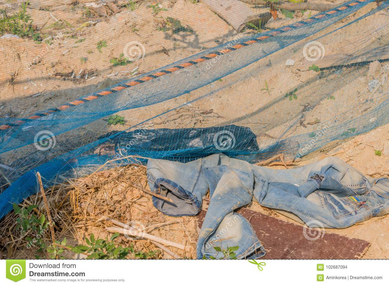Pair of faded bluejeans laying in dirt