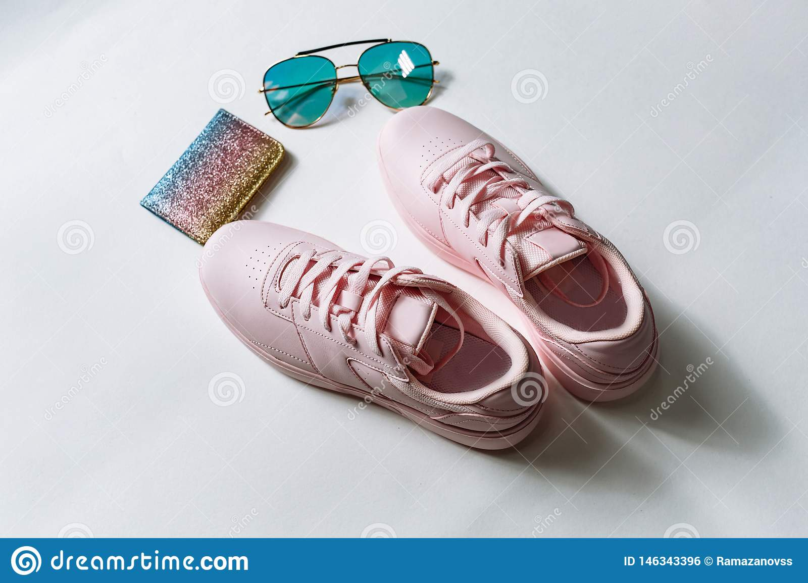 A pair of pink leather sneakers, a purse with multi-colored sequins and sunglasses with blue glass on a white background