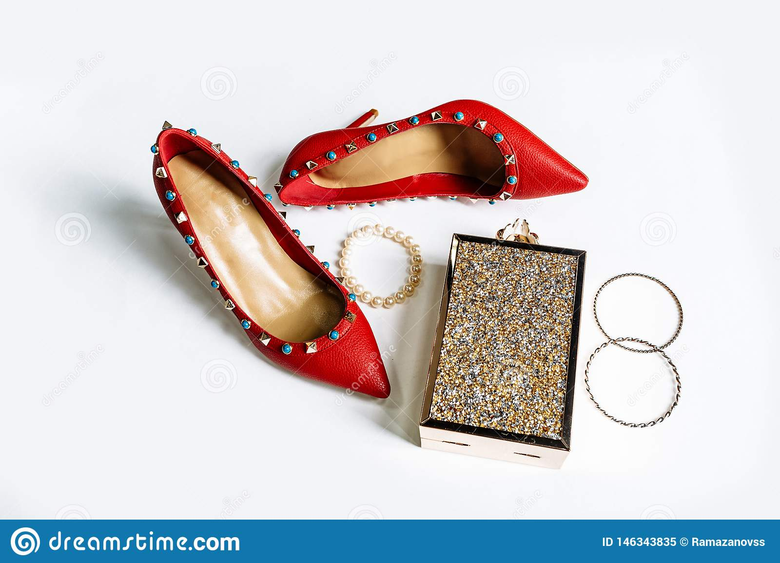 Pair of red high-heeled shoes with pointed toes, decorated with metal blue inserts and metal clutch with sparcles on a white