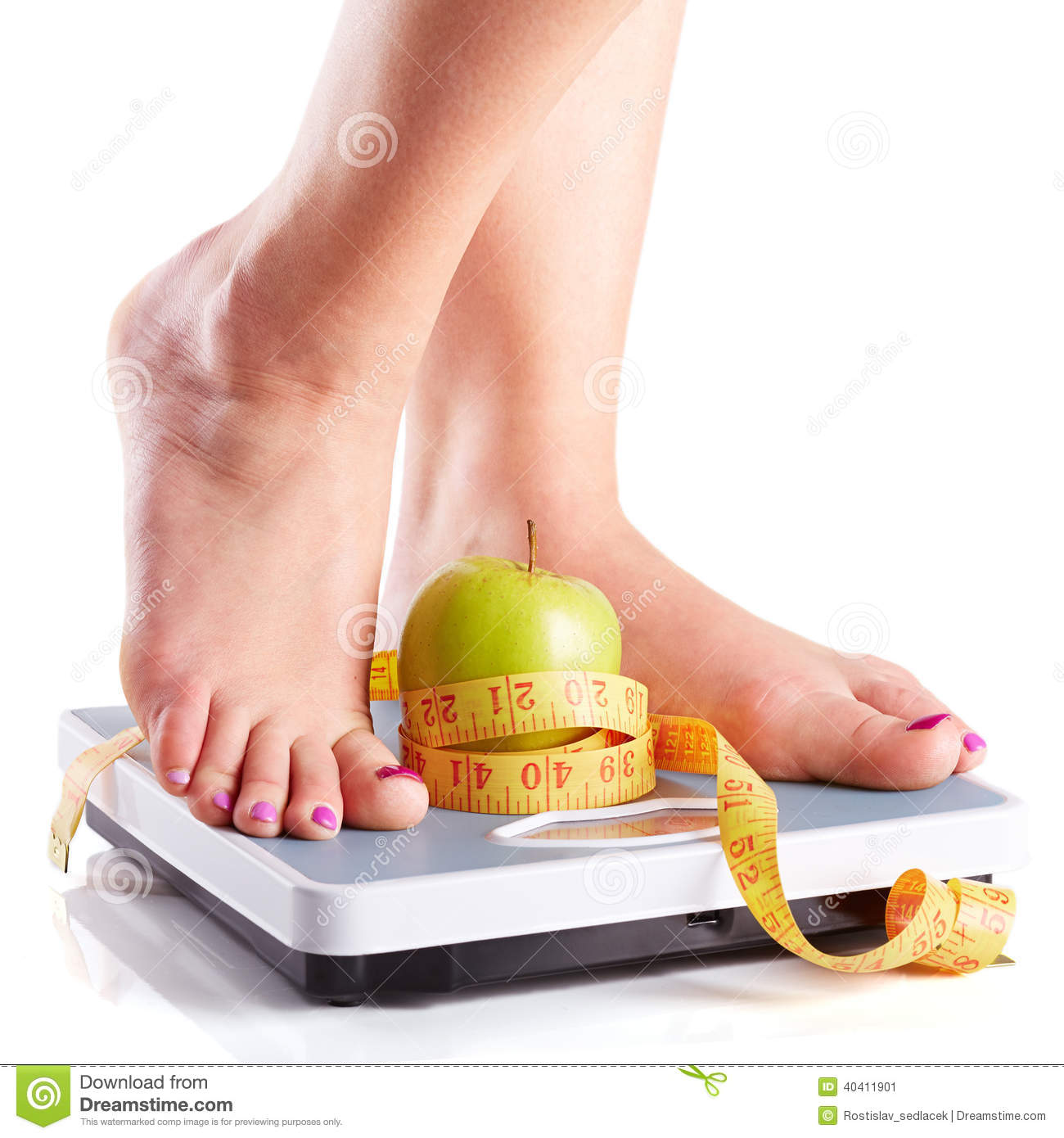A pair of female feet standing on a bathroom scale with green ap
