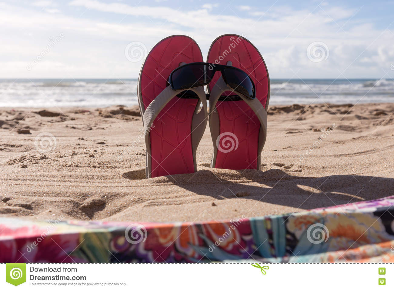 Pair flip flops with sunglasses in the sand of beach