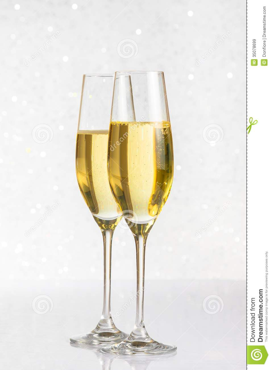 a pair of flutes of golden champagne on silver bokeh. Black Bedroom Furniture Sets. Home Design Ideas