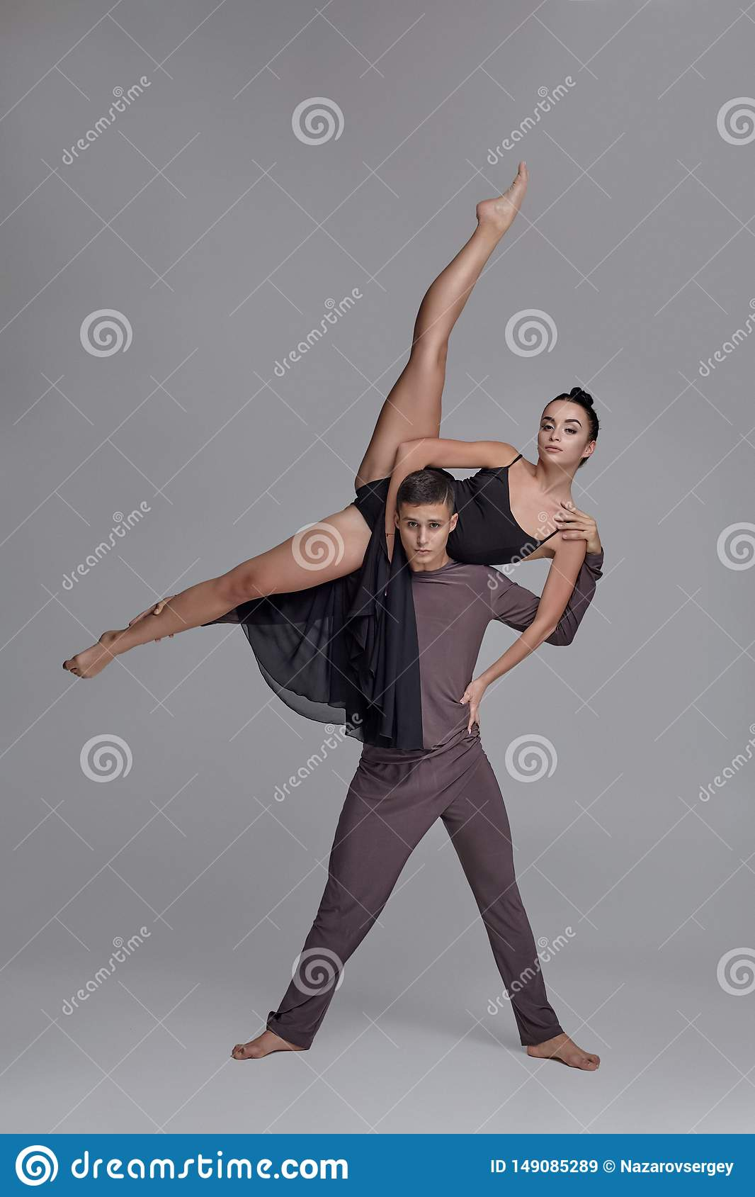Two Athletic Modern Ballet Dancers Are Posing Against A Gray Studio  Background. Stock Image - Image of muscular, ballet: 149085289