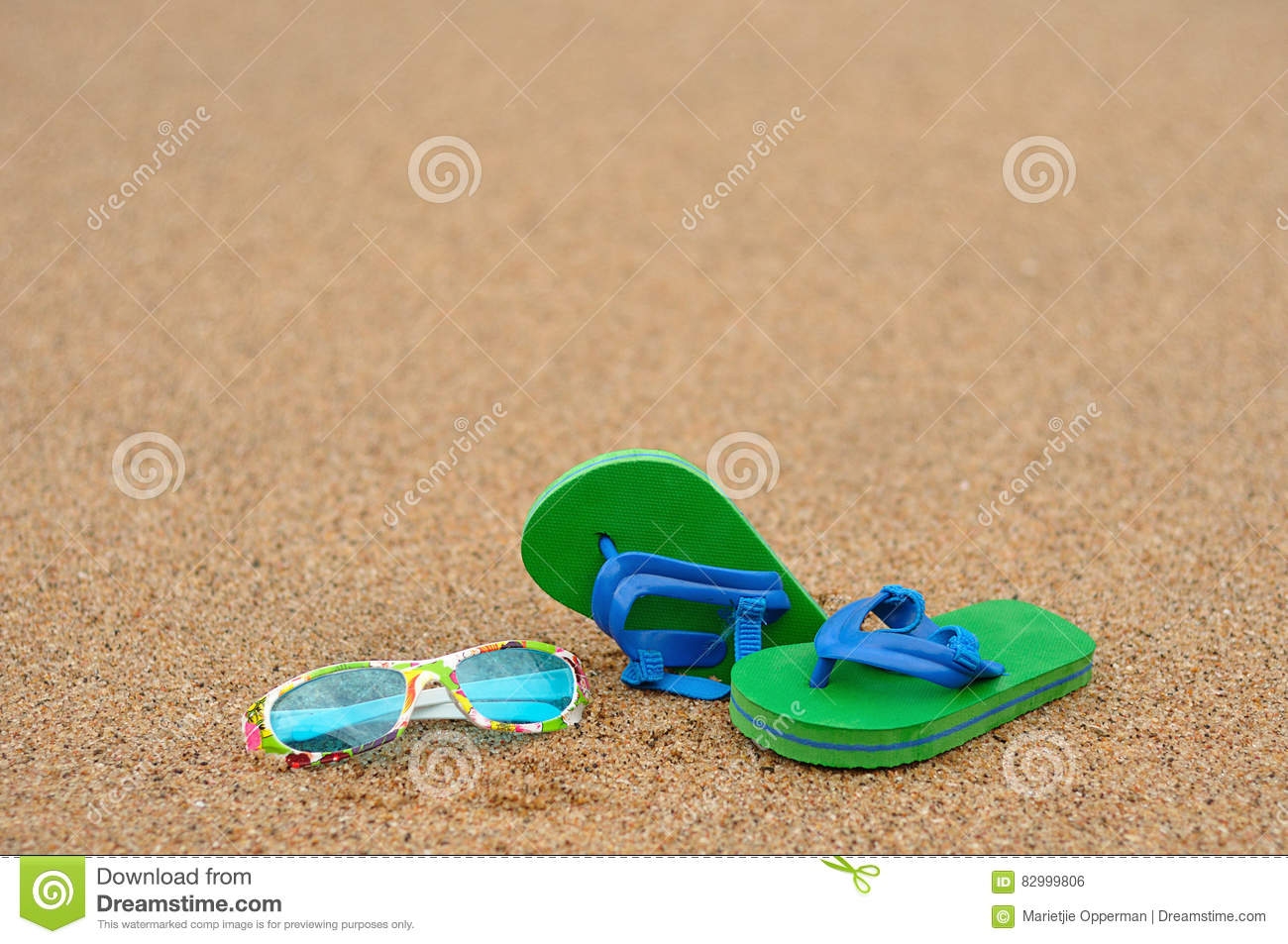 A pair of green and blue flip flops with colorful sunglasses