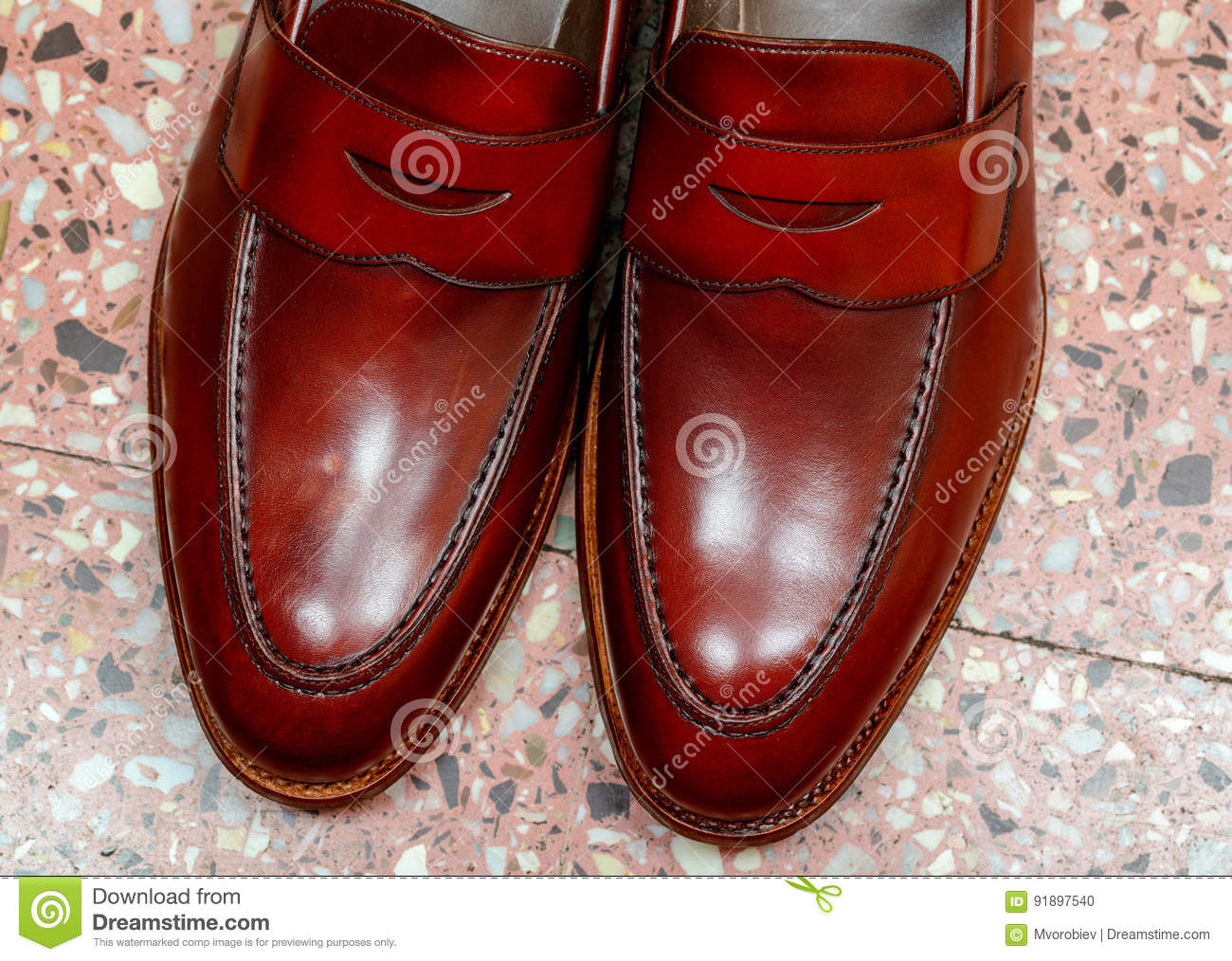 5e3f48abeb1 Pair of leather burgundy penny loafer shoes together on floor background one  by one. Horizontal close-up image