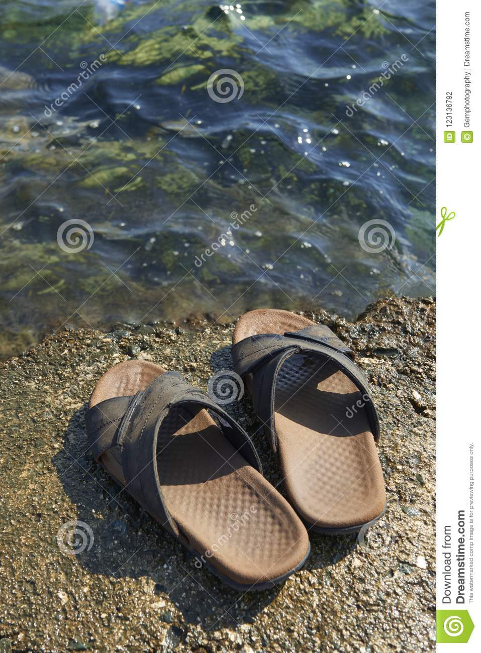 6a20c6a42 A pair of mens leather sandals on water s edge by sea