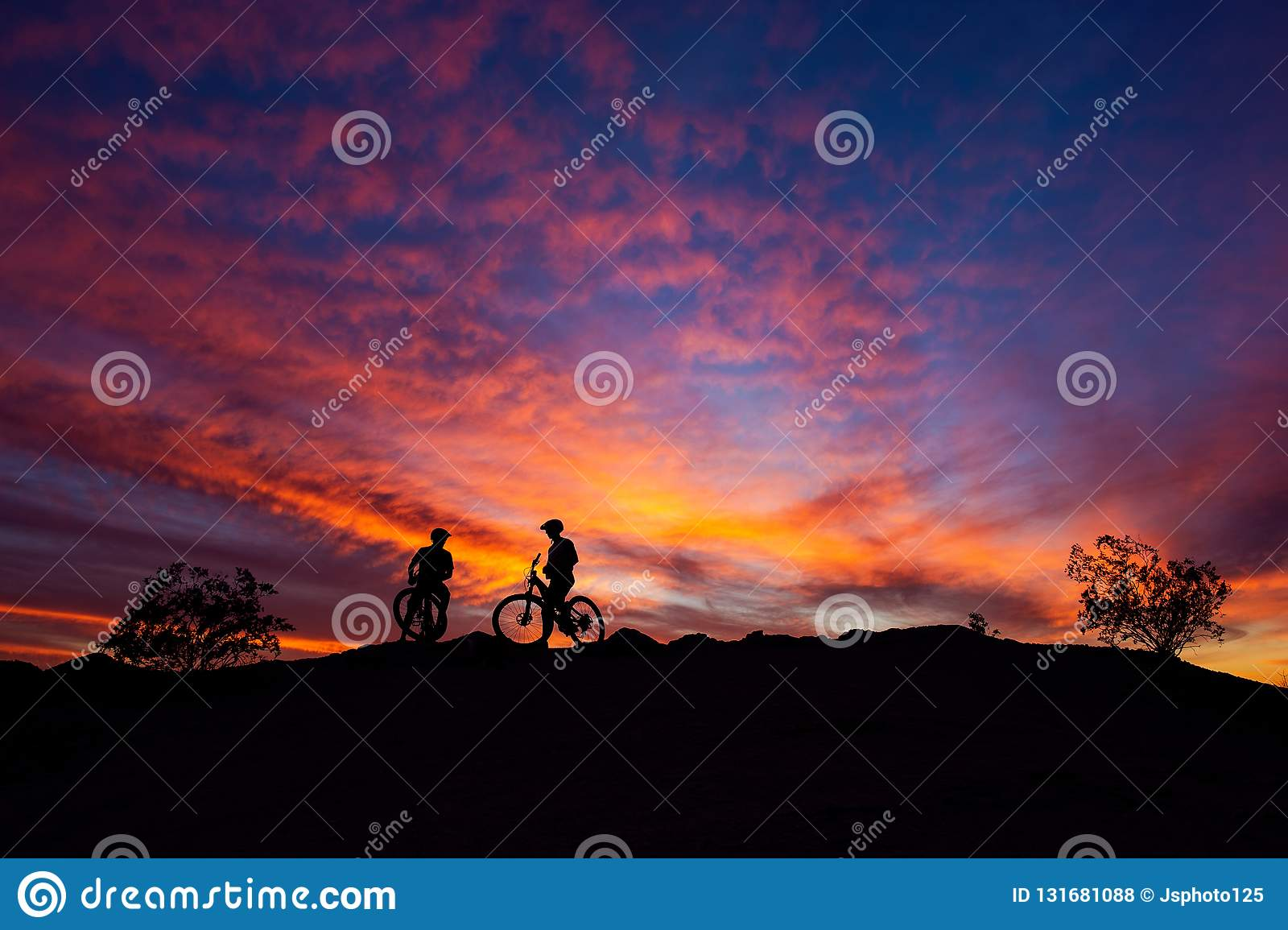 Mountain bikers silhouetted against a colorful sunset sky in South Mountain Park, Phoenix, Arizona.