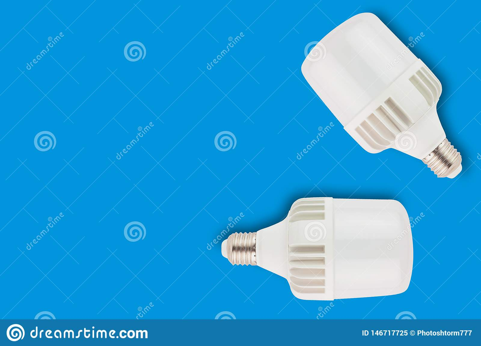 Pair of new plastic led bulbs on blue background with copy space. Saving and economy or green energy concept