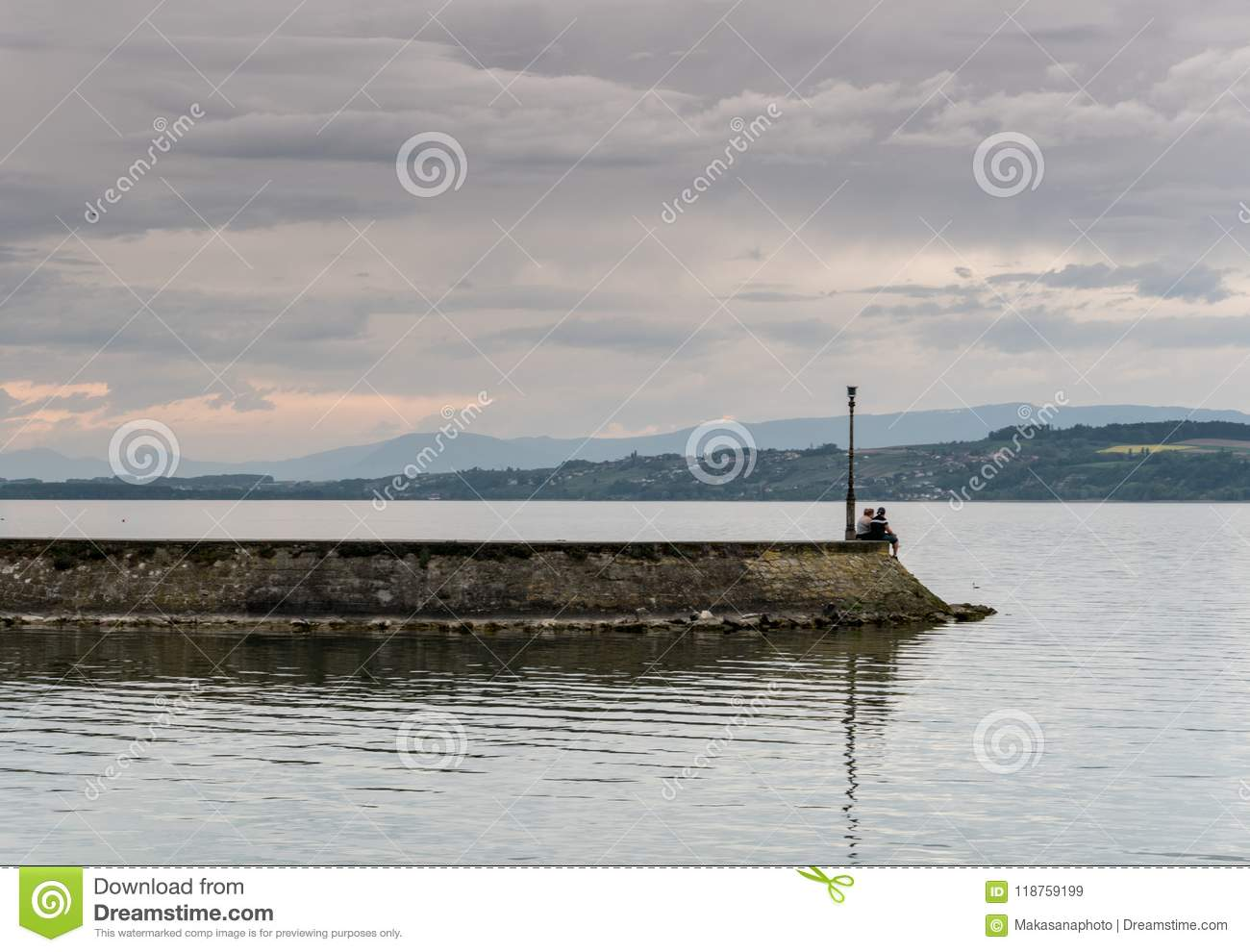 Young lovers sitting at the end of a long pier and admiring the view of a gorgeous lake and mountain landscape in the evening