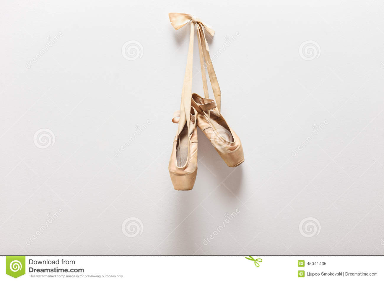 pair of old ballet shoes hanging on a wall stock image