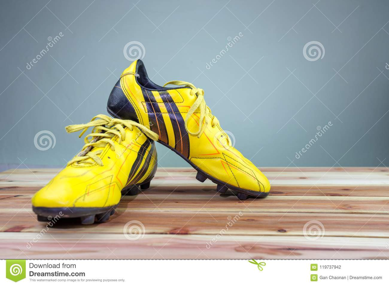 81494ed6f A pair of old football boots old yellow football shoes placed on a wooden  board, gray background Soft light