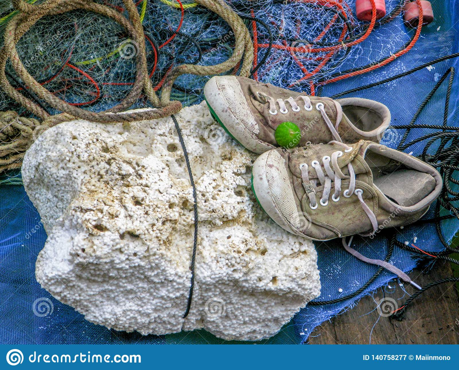 Pair of old sneakers on white foam with fishnet and red rope on the fishing boat.