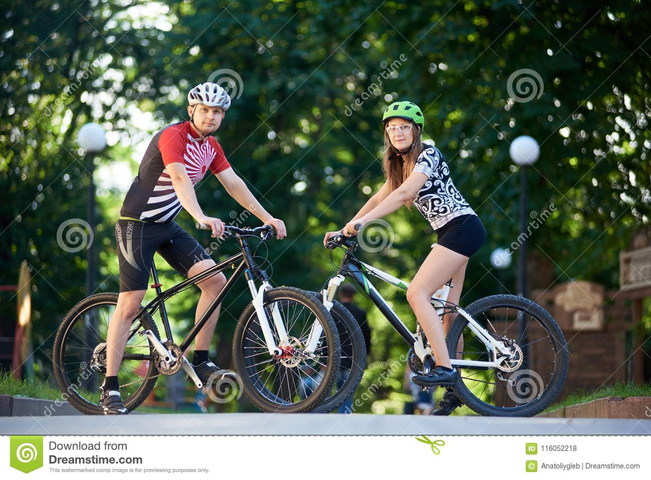 Pair of professional cyclists in cycling clothing stopped to pose for  photo. Woman and men looking to the camera f78557d70
