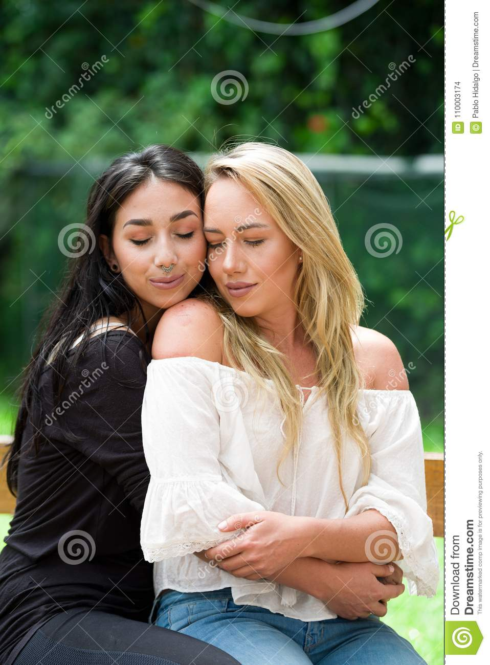 A Pair Of Proud Lesbian In Outdoors, Brunette Woman Is Hugging A Blonde Woman, In A -9361